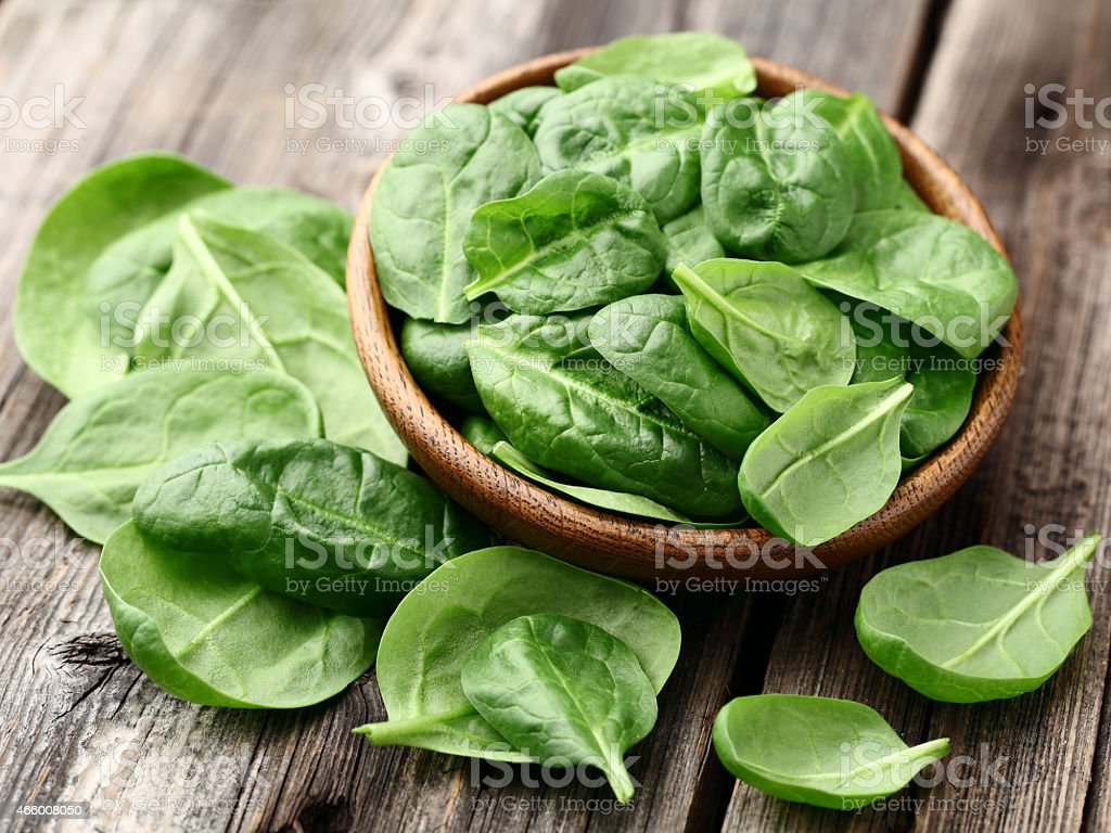 Fresh baby spinach leaves in a bowl on a wooden table stock photo