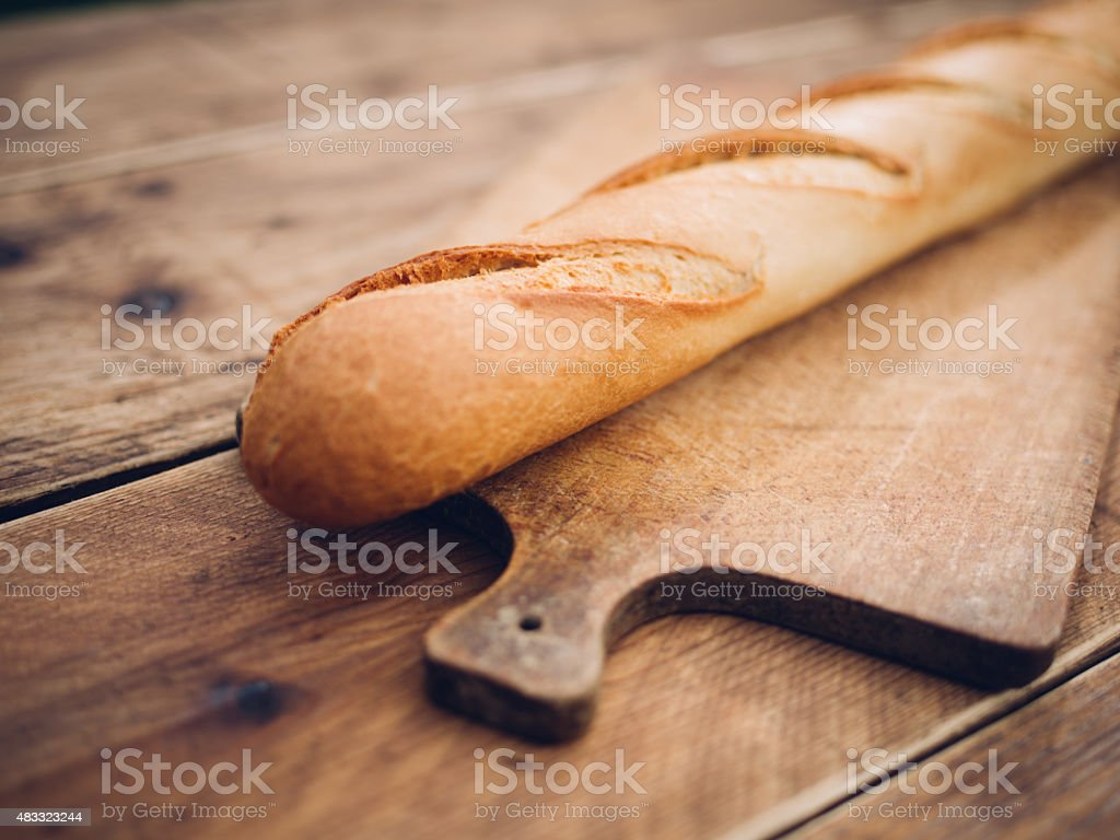 Fresh baguette lying on a vintage wooden board stock photo