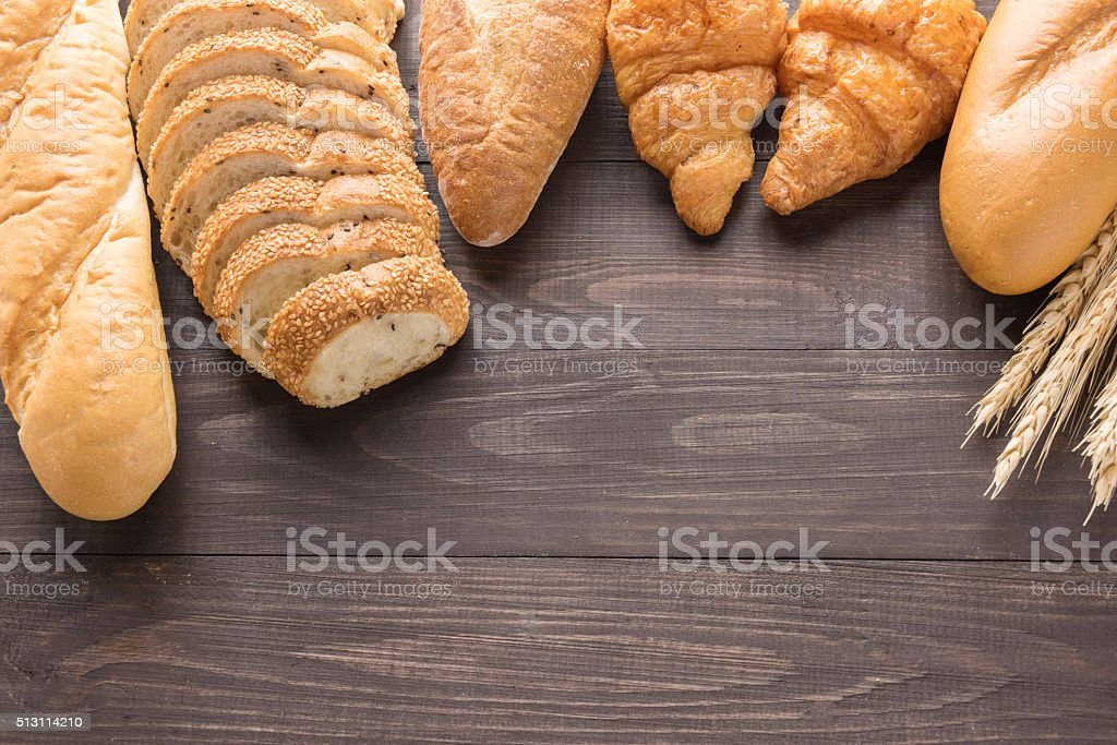 Fresh baked bread and wheat on wooden background stock photo