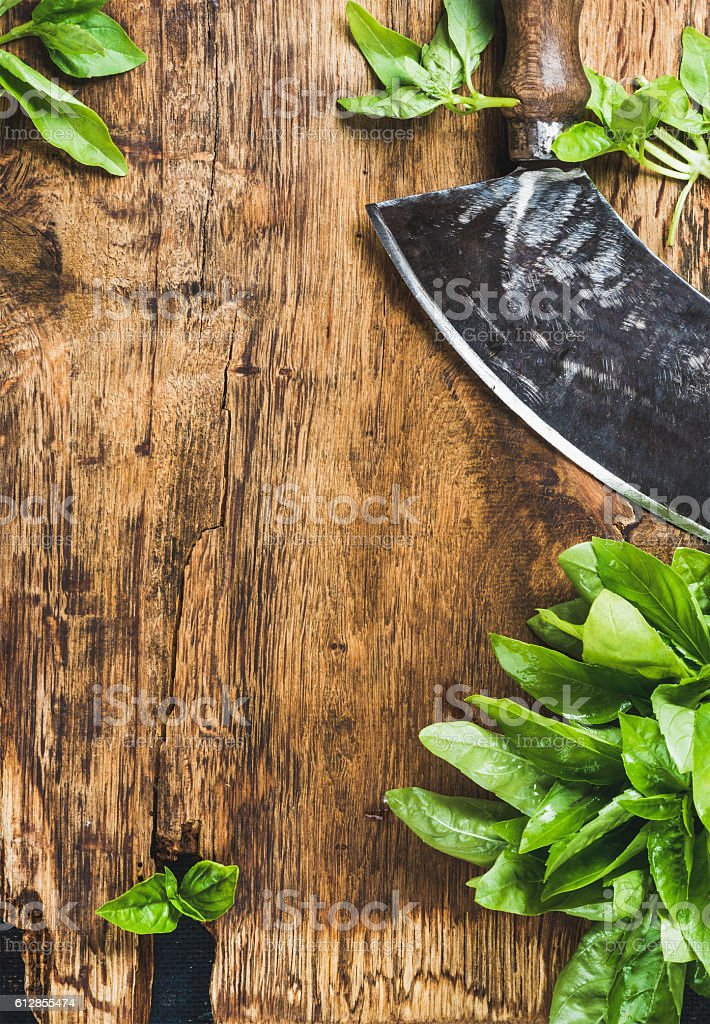 Fresh basil and vintage herb chopper on rustic wooden bord stock photo