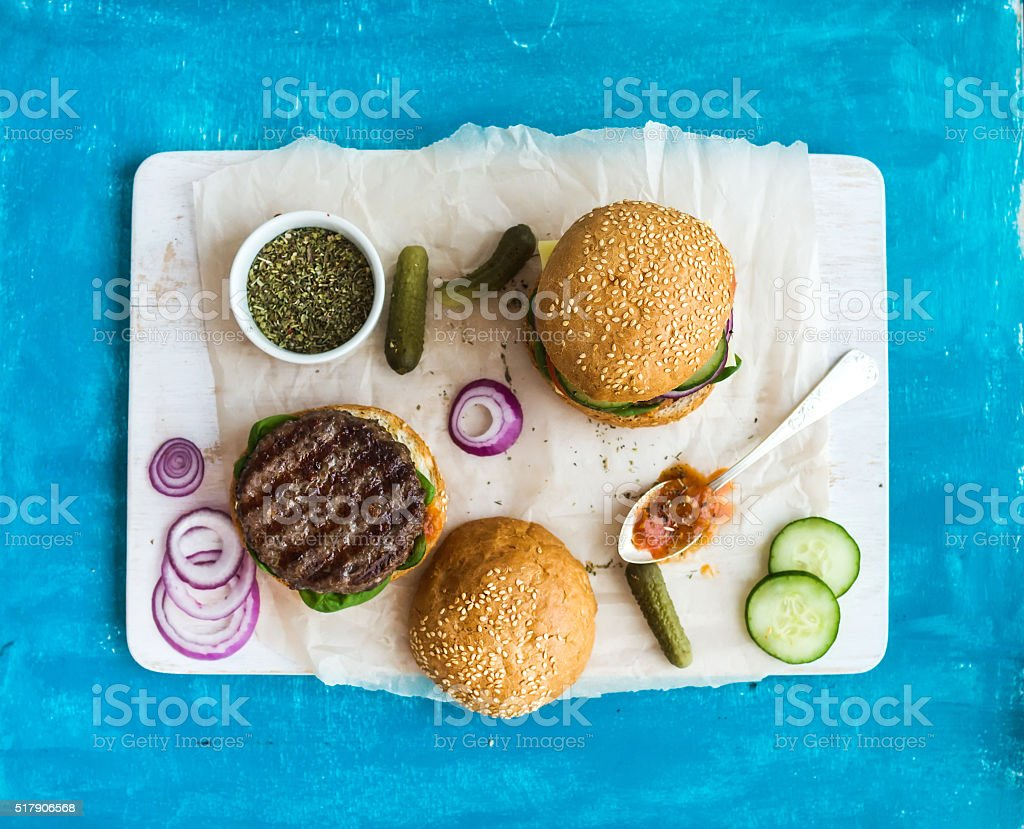 Fresh beef burger with cheese, vegetables, spicy tomato sauce on stock photo