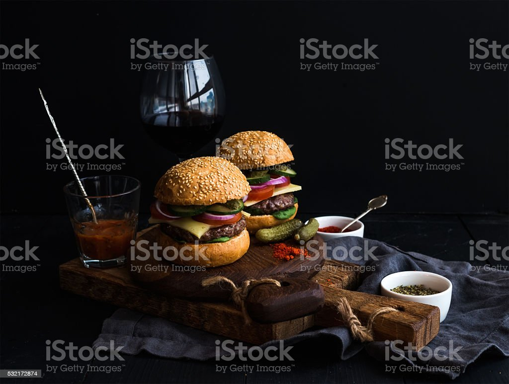 Fresh beef burgers on rustic wooden boards with glass of stock photo