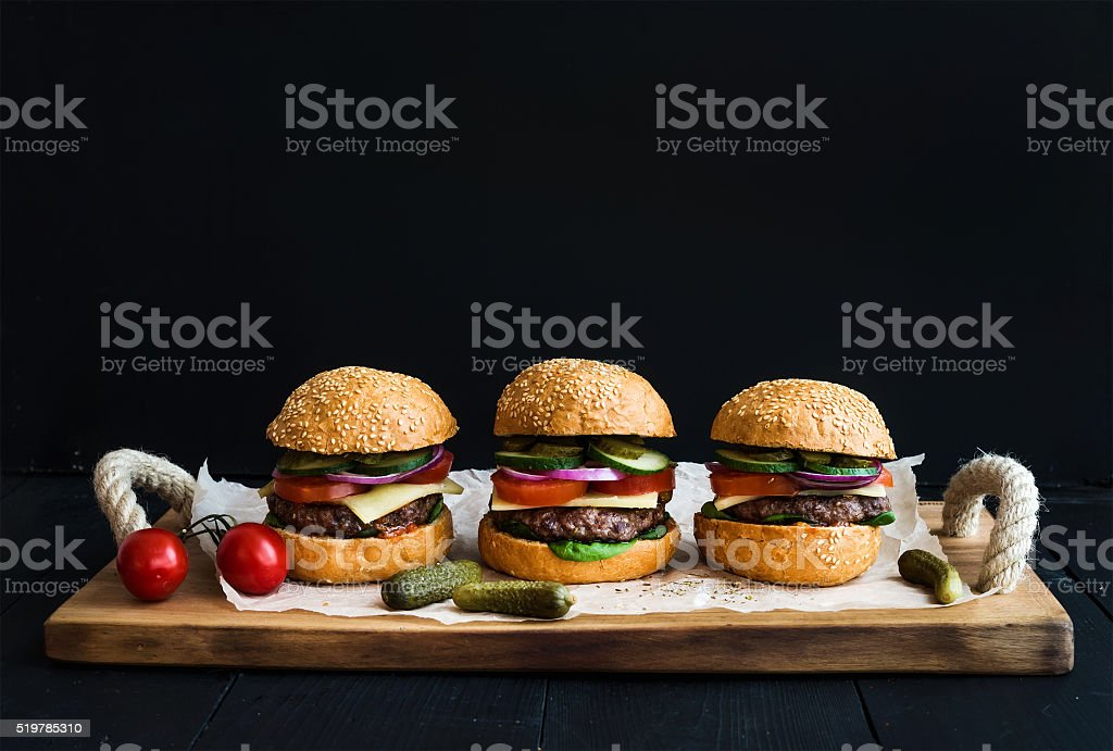Fresh beef burgers with cheese, vegetables, pickles and spicy tomato stock photo