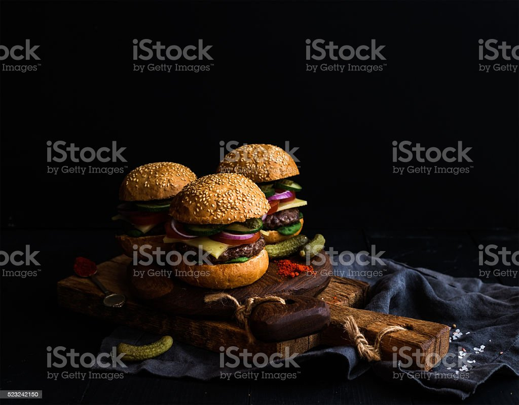 Fresh beef burgers with pickles and spices on rustic wooden stock photo