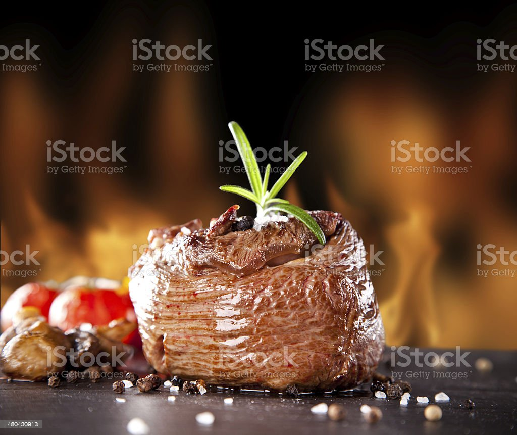 Fresh beef steak on black stone and fire stock photo