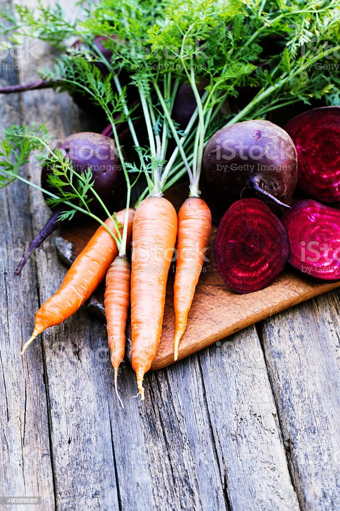 Fresh beet and carrots on wooden background stock photo