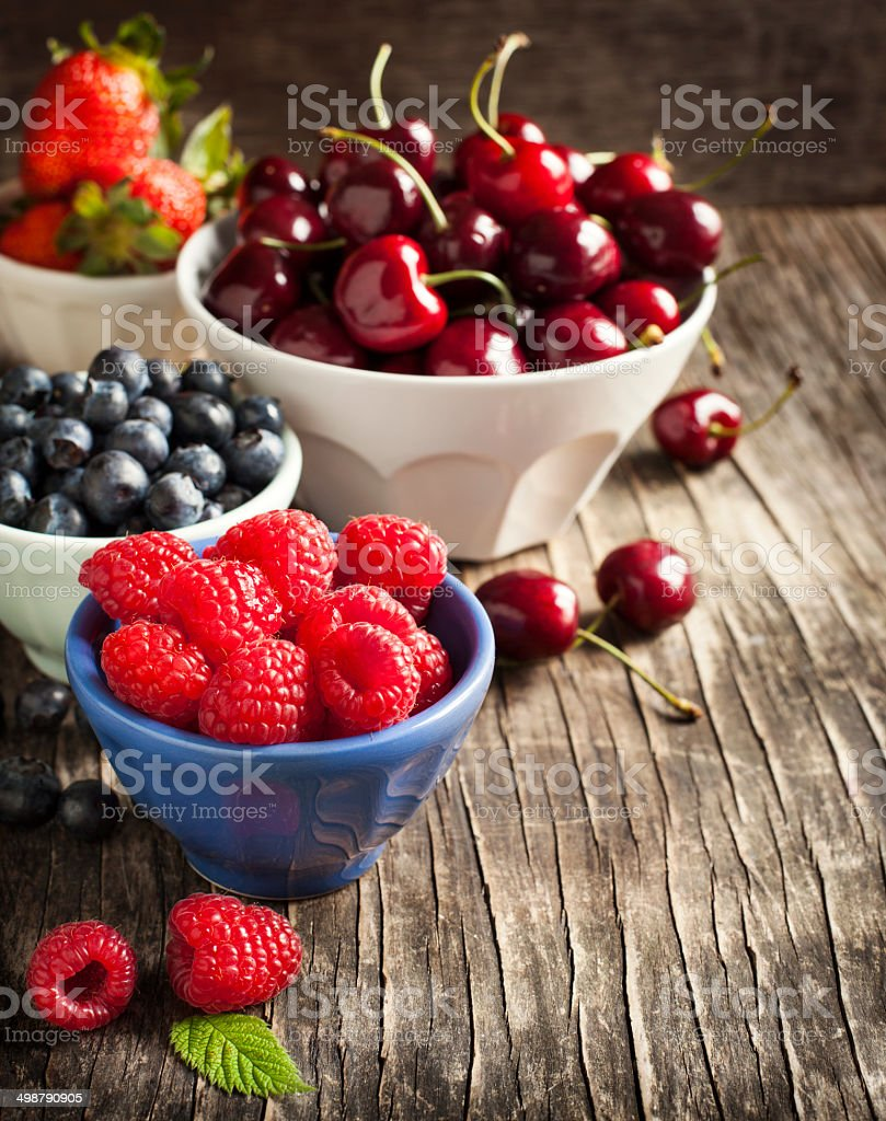Fresh berries in bowls on wooden background. stock photo