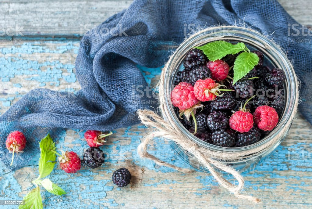 Fresh berries of raspberries and blackberries in a glass jar on a wooden table, top view stock photo