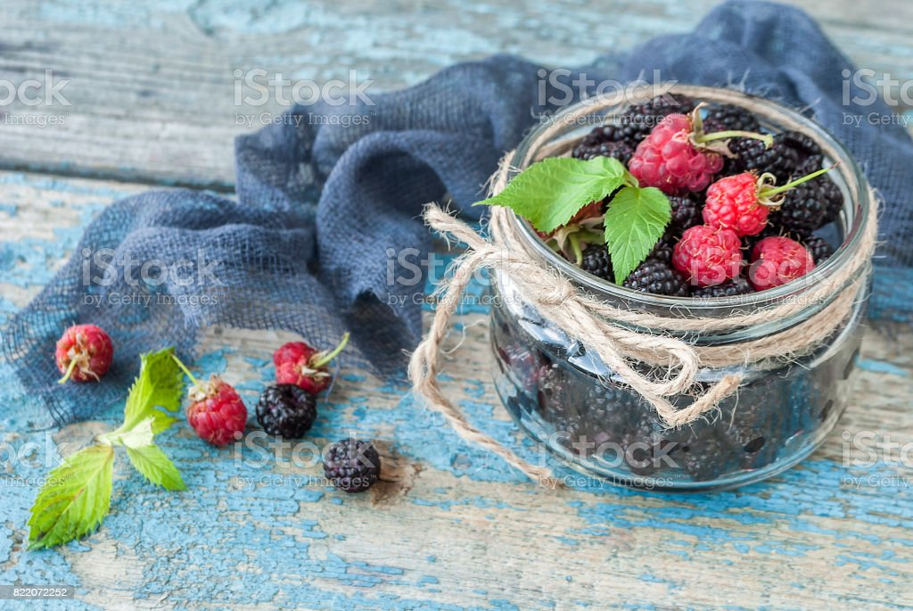 Fresh berries of raspberries and blackberries in a glass jar on a wooden table stock photo