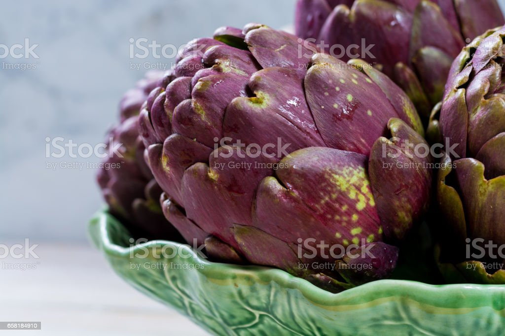 Fresh big Romanesco artichokes green-purple flower heads ready to cook stock photo
