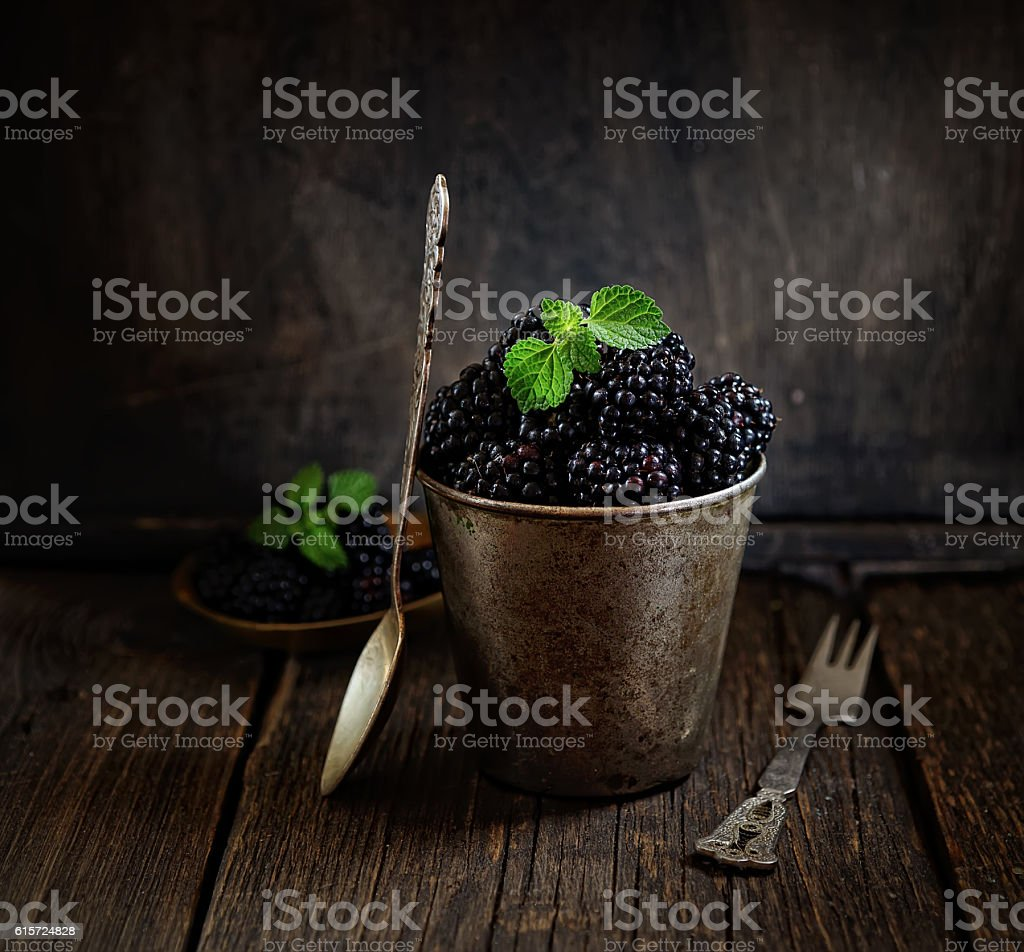 Fresh blackberries in a bucket on a wooden background. rustic style stock photo