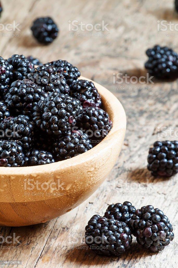 Fresh blackberries in a wooden bowl stock photo