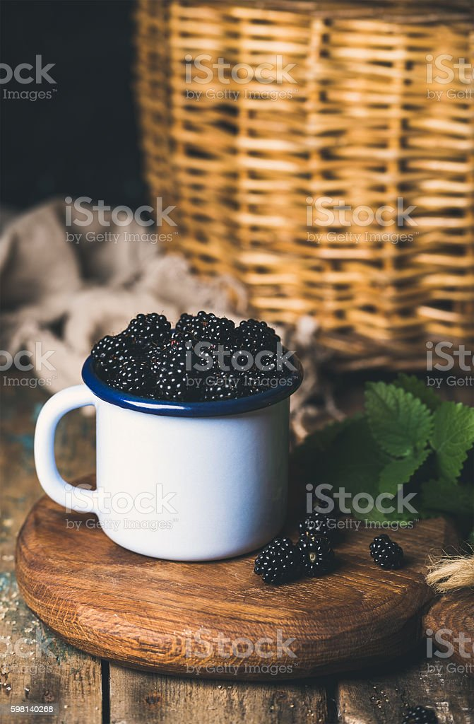 Fresh Blackberries in white cup on round serving wooden stock photo