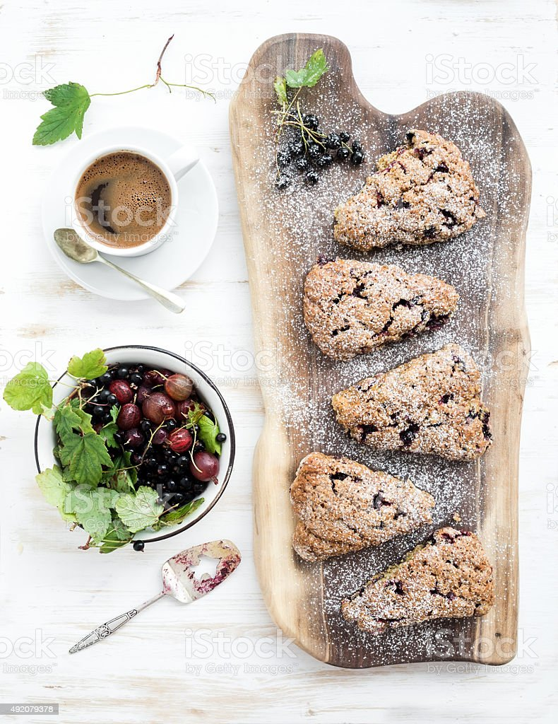 Fresh black-currant scones with coffee and bowl of berries stock photo