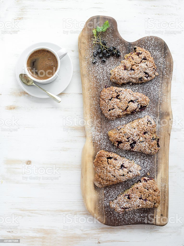 Fresh black-currant scones with cup of coffee , top view stock photo