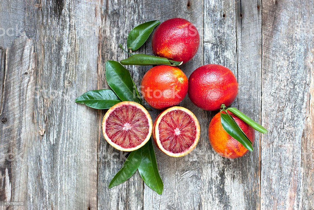 Fresh blood oranges on wooden background stock photo