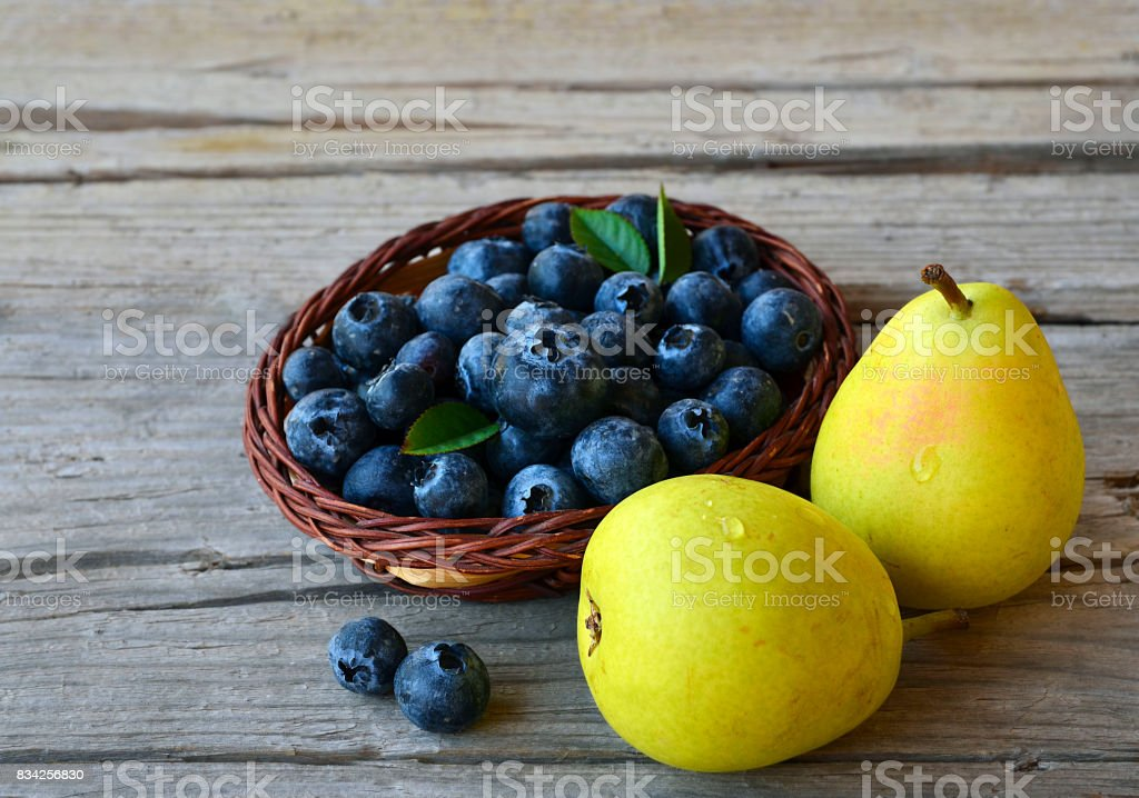 Fresh blueberries and ripe pears on wooden rustic table. Blueberry and pears.Healthy eating,diet and nutrition concept. stock photo