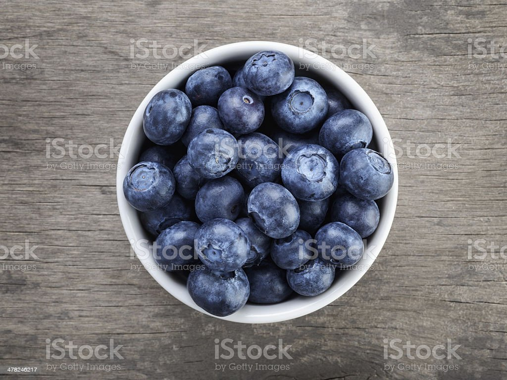 fresh blueberries in white bowl on wood table stock photo