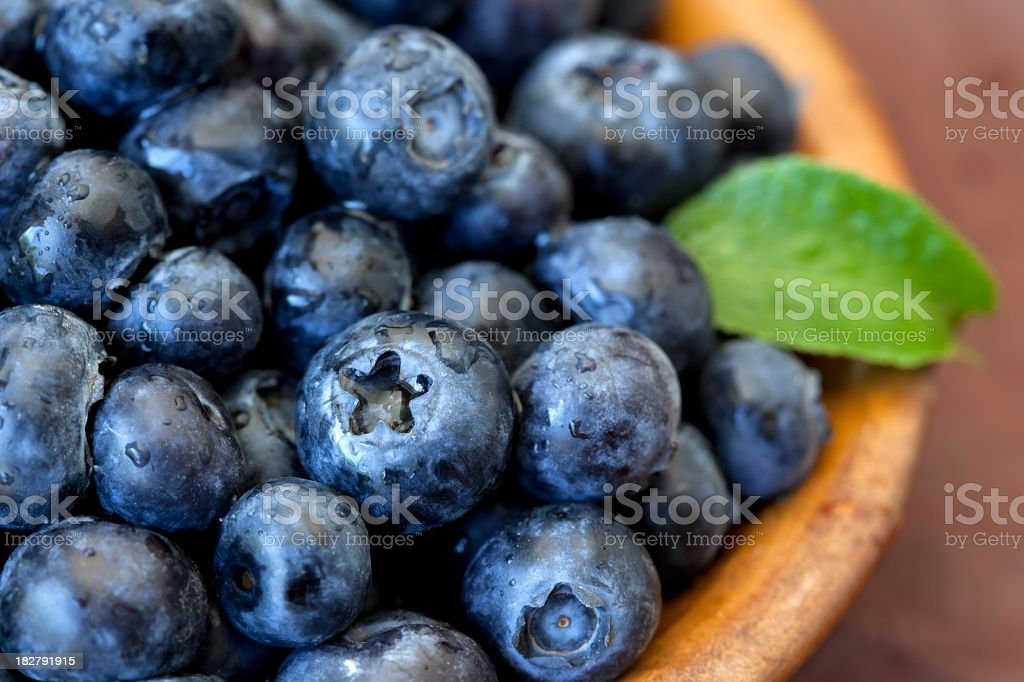 Fresh blueberries with green leaf accent in bowl stock photo