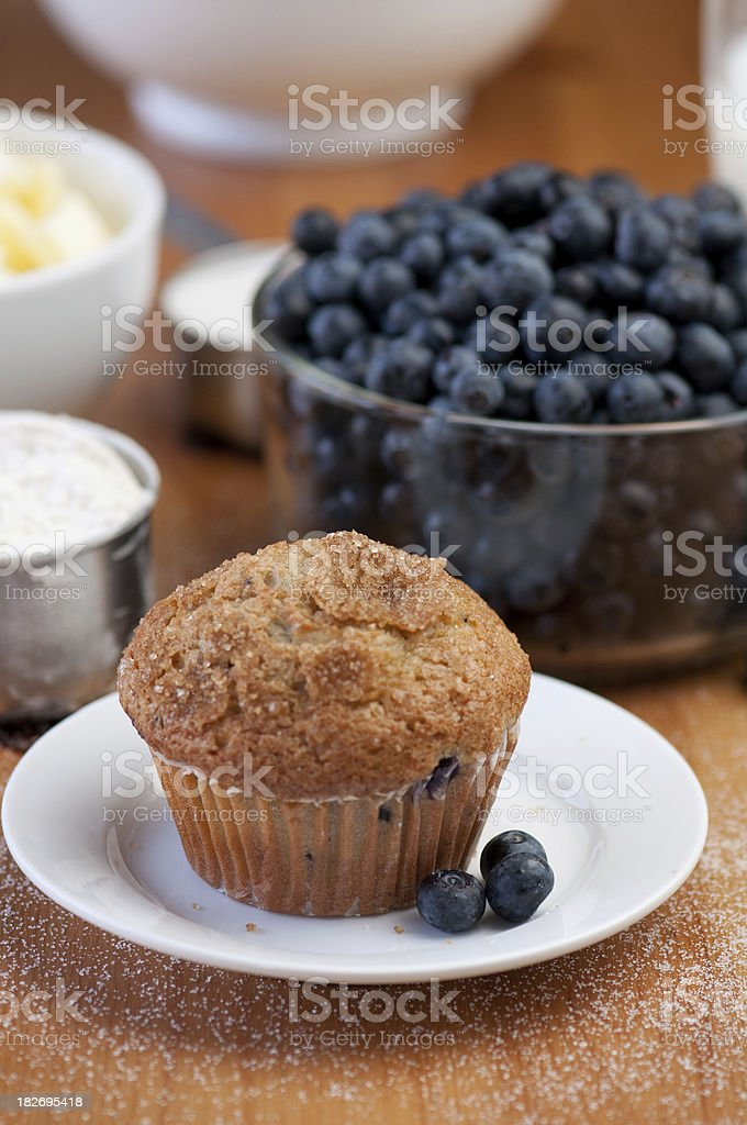 Fresh blueberry muffin on plate baking ingredients in the background royalty-free stock photo