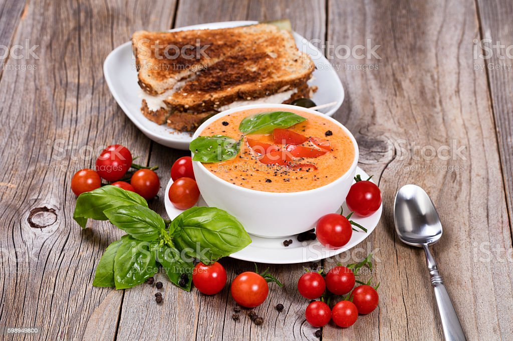 Fresh bowl of creamy tomato soup and sandwich stock photo