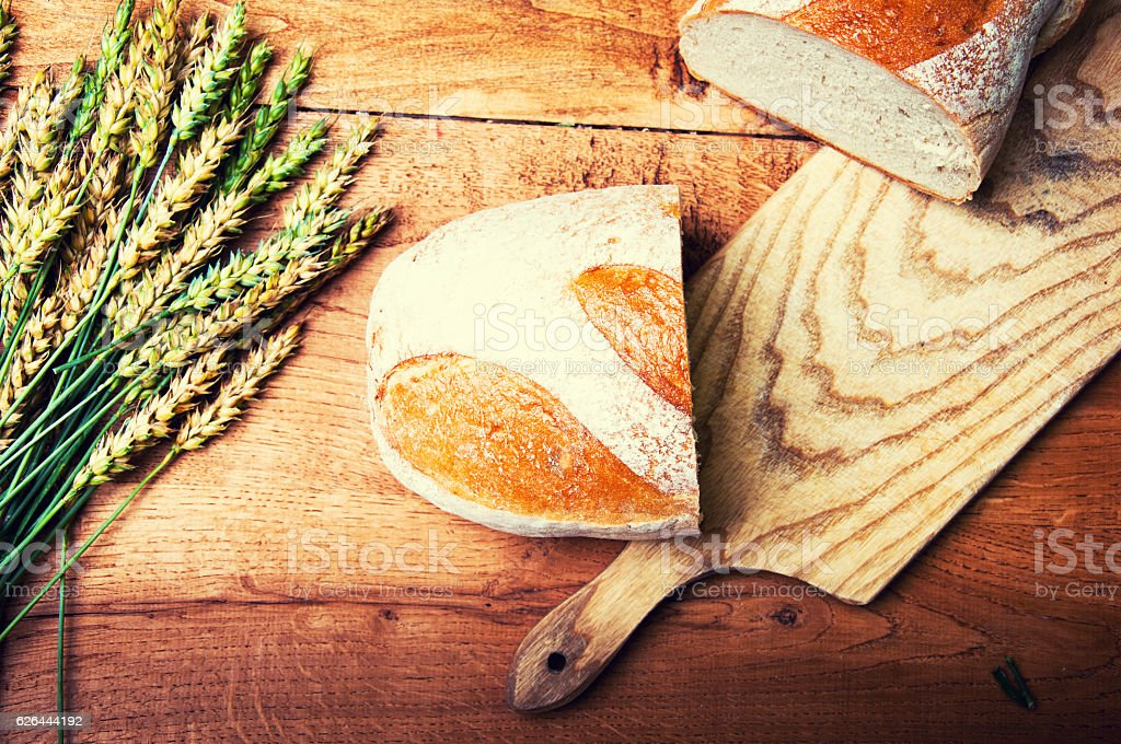 Fresh bread and wheat on wooden background stock photo