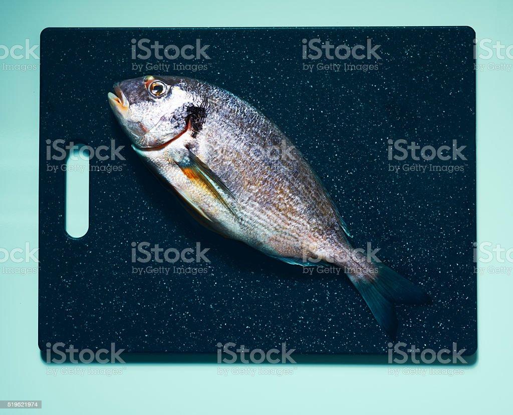 fresh bream on cutting board stock photo