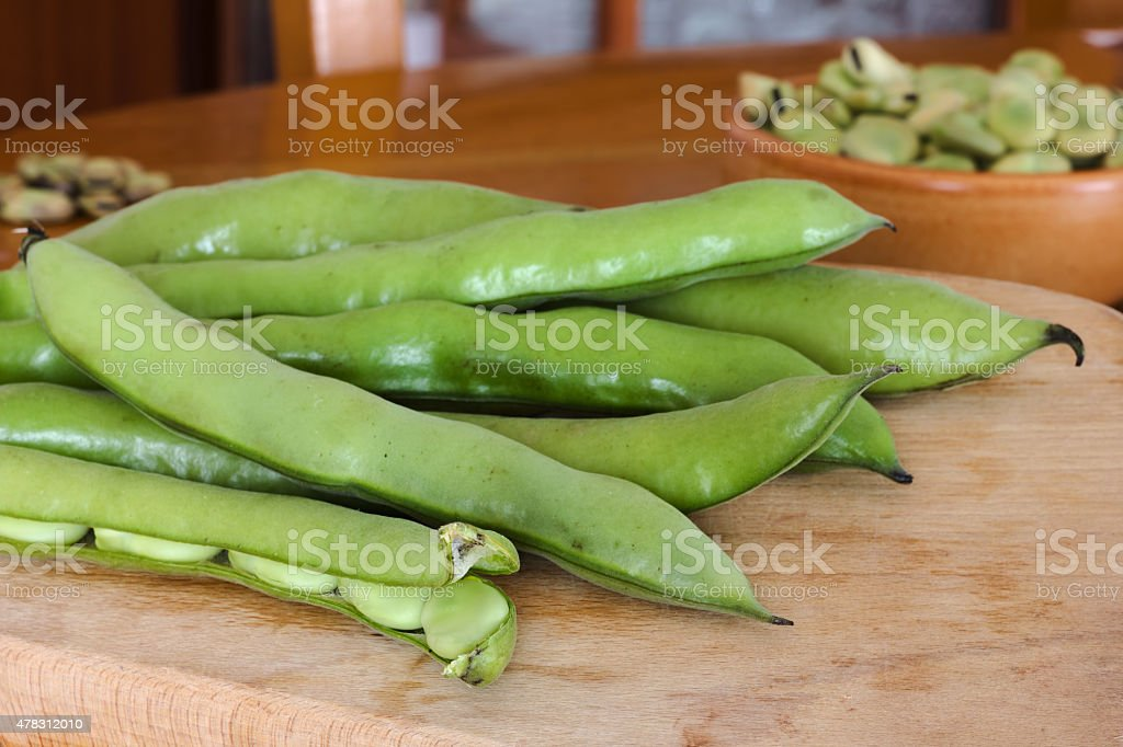 Fresh broad beans fava on wood table stock photo