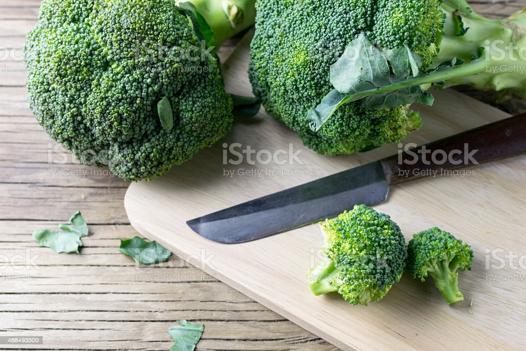 fresh broccoli on a cutting board and knife stock photo