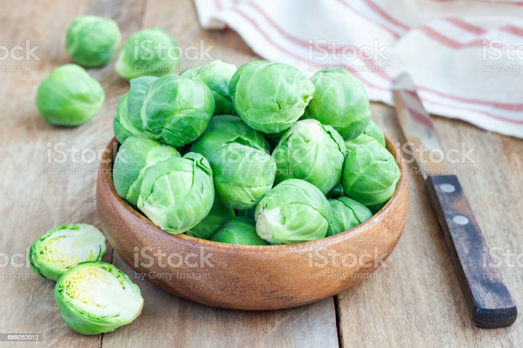 Fresh brussels sprouts in bowl on wooden background, horizontal stock photo