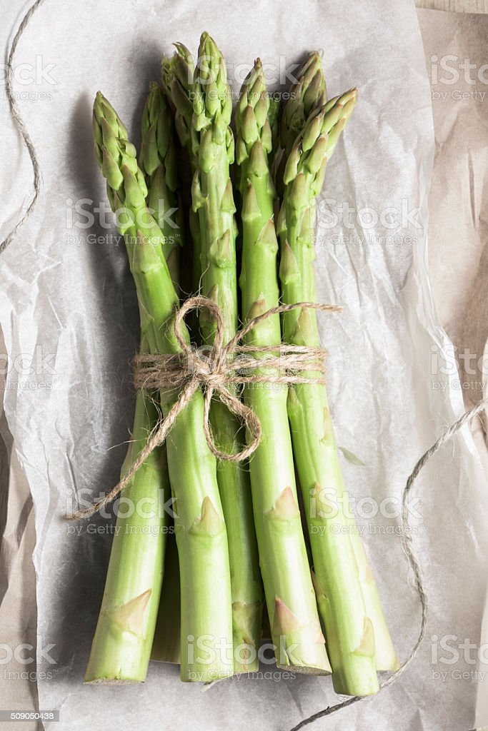 Fresh bunch of green asparagus spears tied with rustic string stock photo