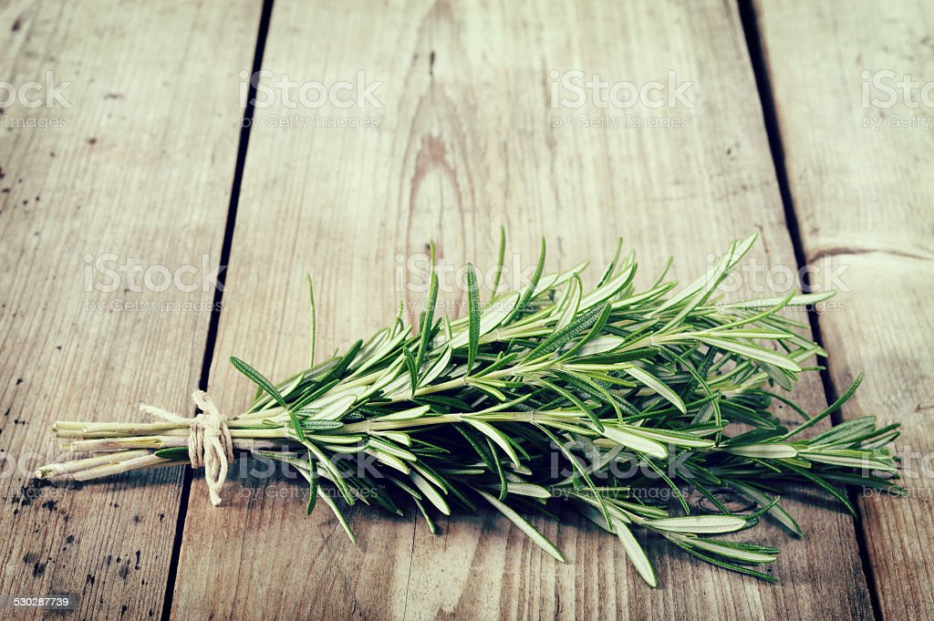 Fresh bunch of rosemary on wooden table. stock photo