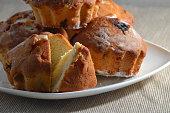 Fresh buns with raisins on a white plate close-up.