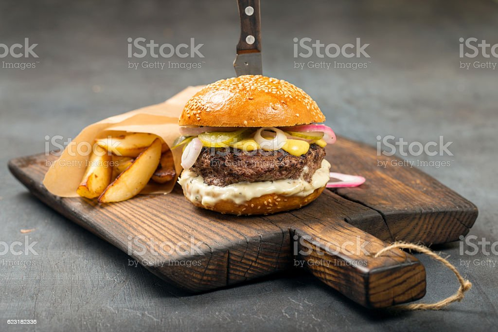 Fresh burger with fries on the old board stock photo