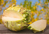 fresh cabbage kohlrabi on a dark wooden table with blurred