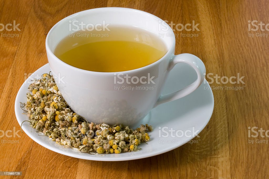 Fresh camomile seeds surrounding a white mug on a wood table royalty-free stock photo
