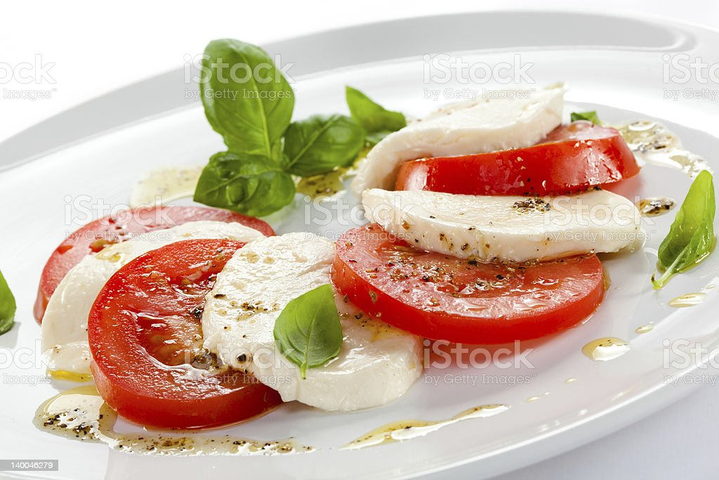 Fresh caprese salad with basil leaves on white plate stock photo