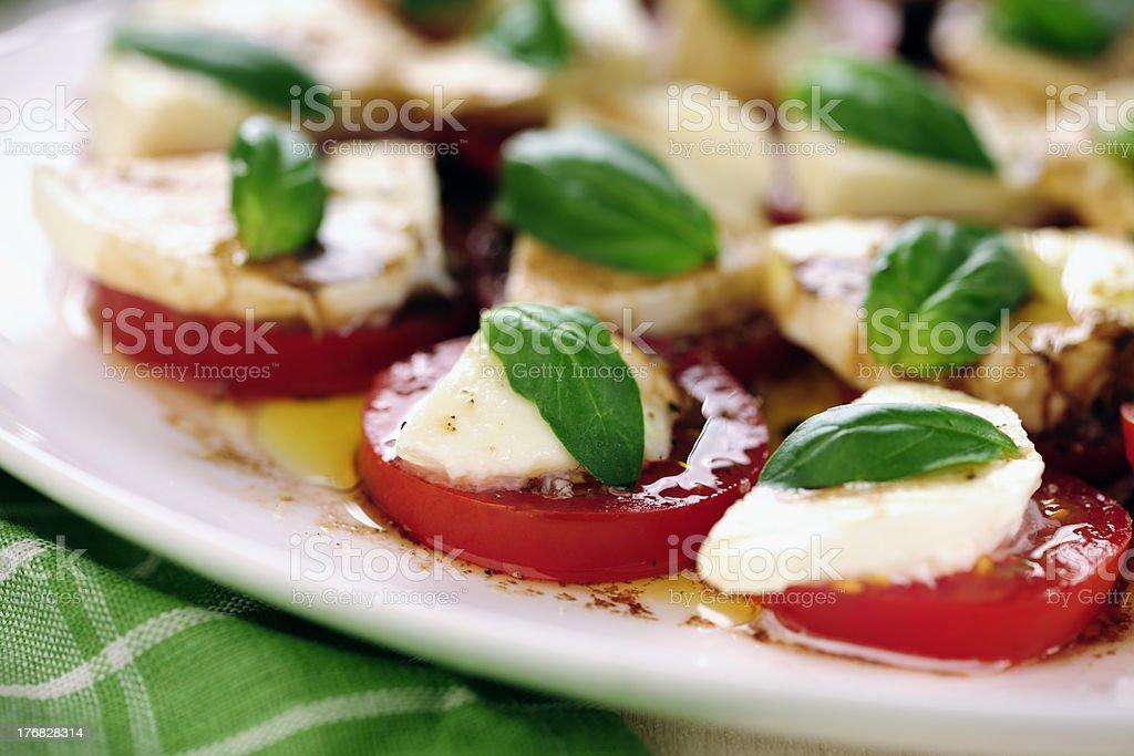 Fresh caprese salad with delicious tomatoes + mozzarella and bas royalty-free stock photo