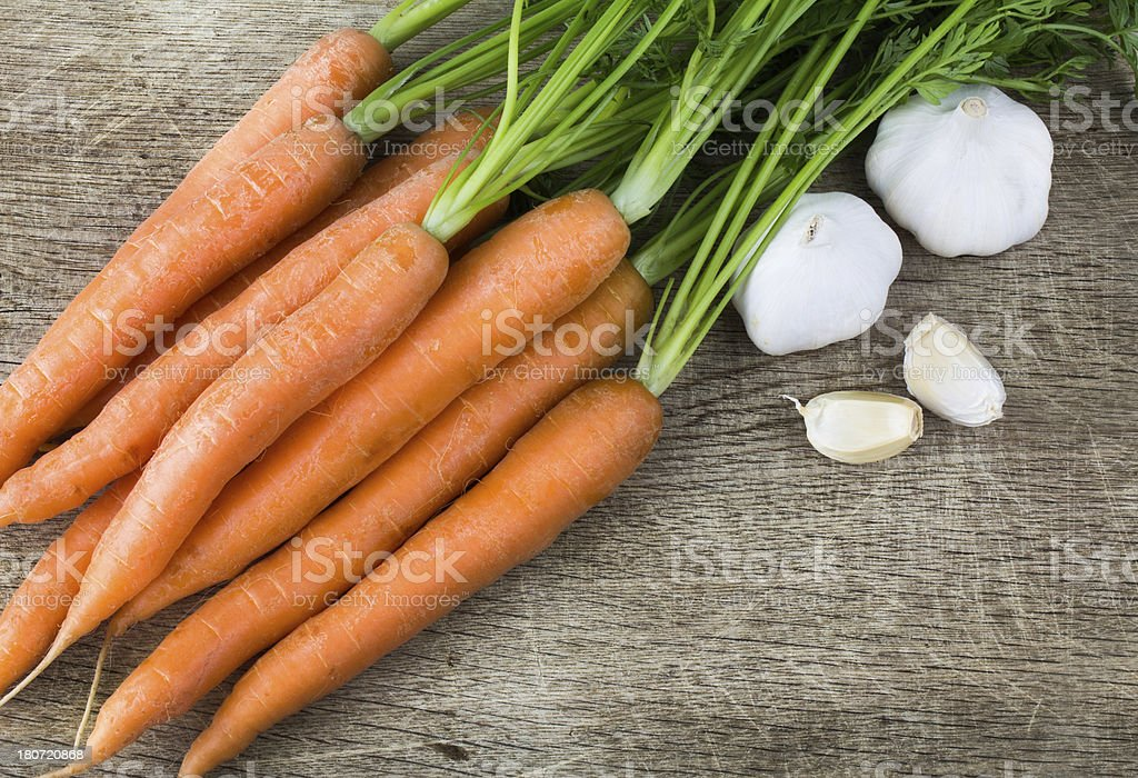Fresh carrot and garlic on old cutting board royalty-free stock photo