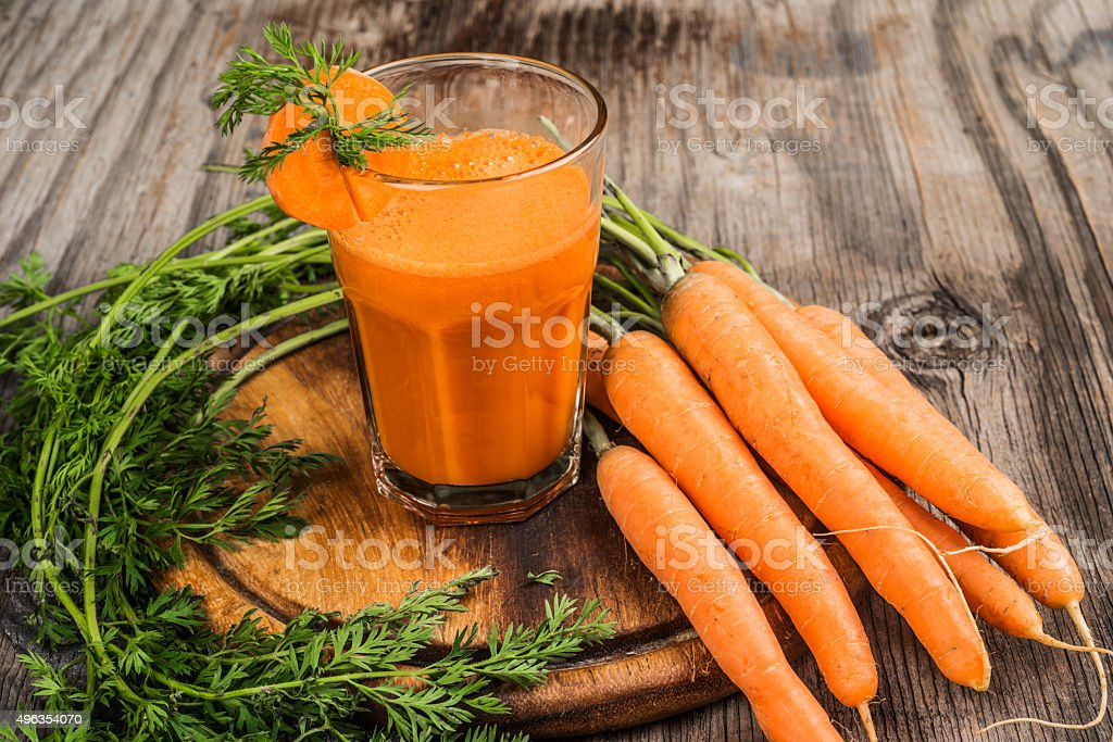 Fresh carrot juice and carrots on chopping board stock photo
