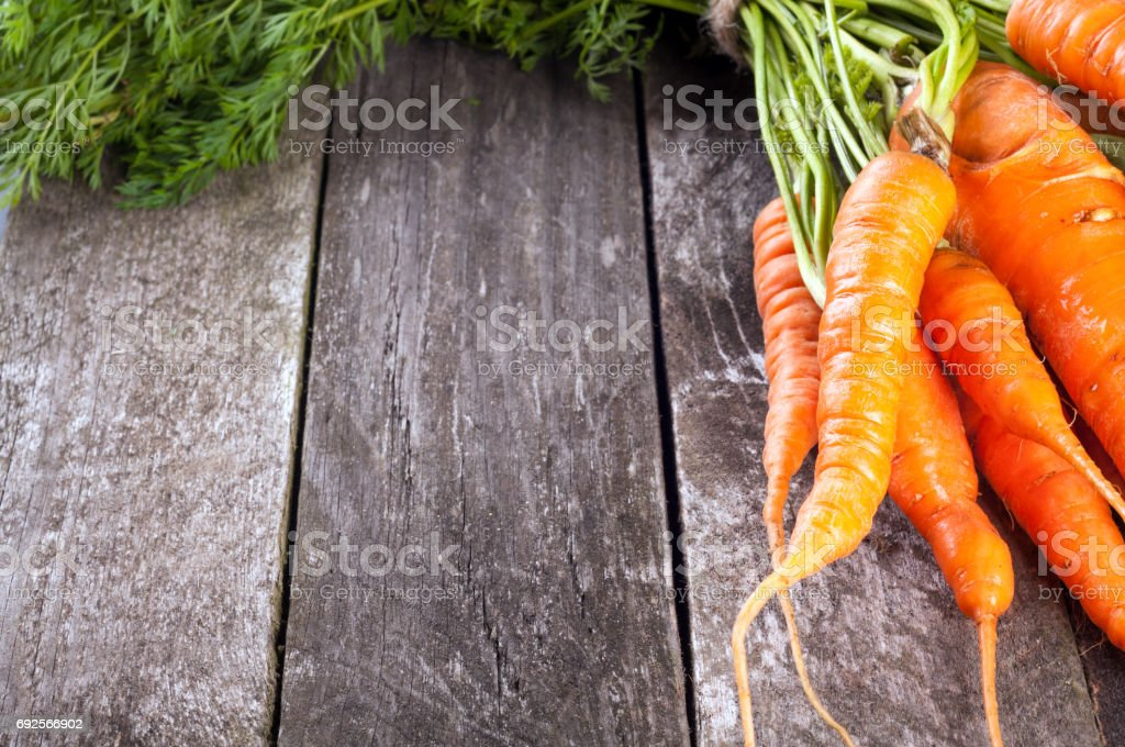Fresh carrots bunch on rustic wooden background. Copy space stock photo