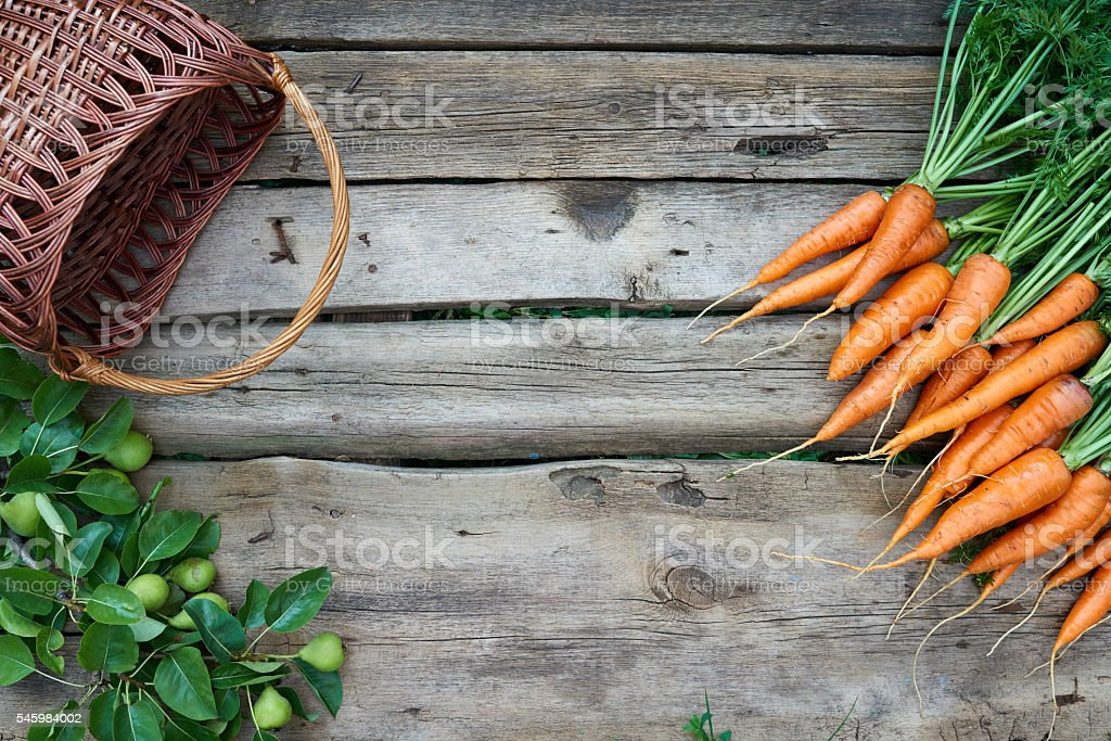 Fresh carrots bunch with empty basket on rustic wooden background stock photo