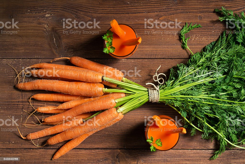 Fresh carrots, glasses of juice on wooden table, top view stock photo