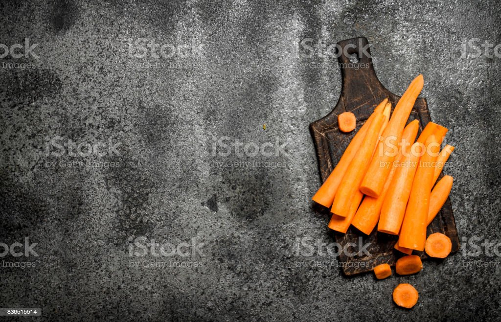 Fresh carrots on the old Board. On rustic background. stock photo