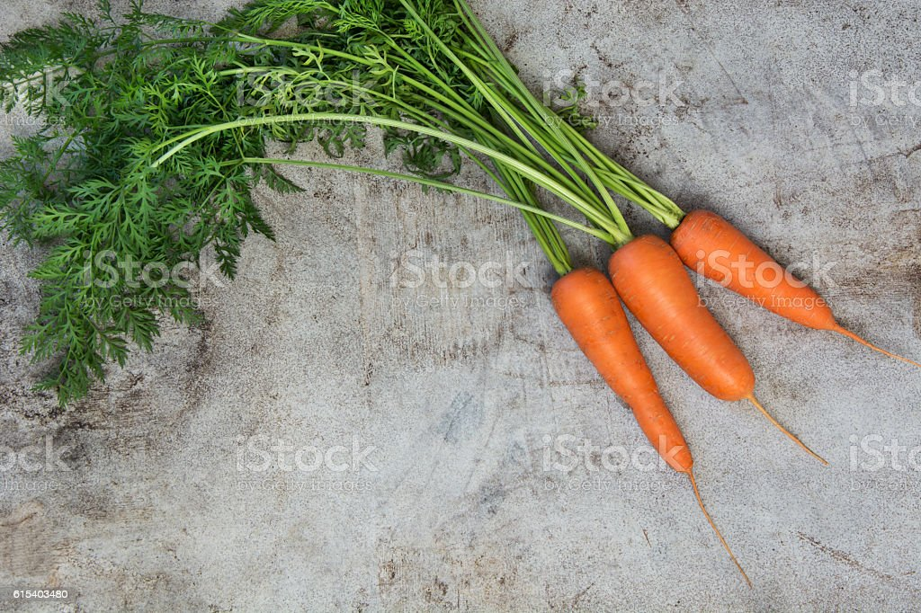 Fresh carrots with green tops on rustic table. Top view. stock photo