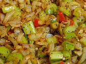 Fresh celery and onions and peppers with spices in a pan