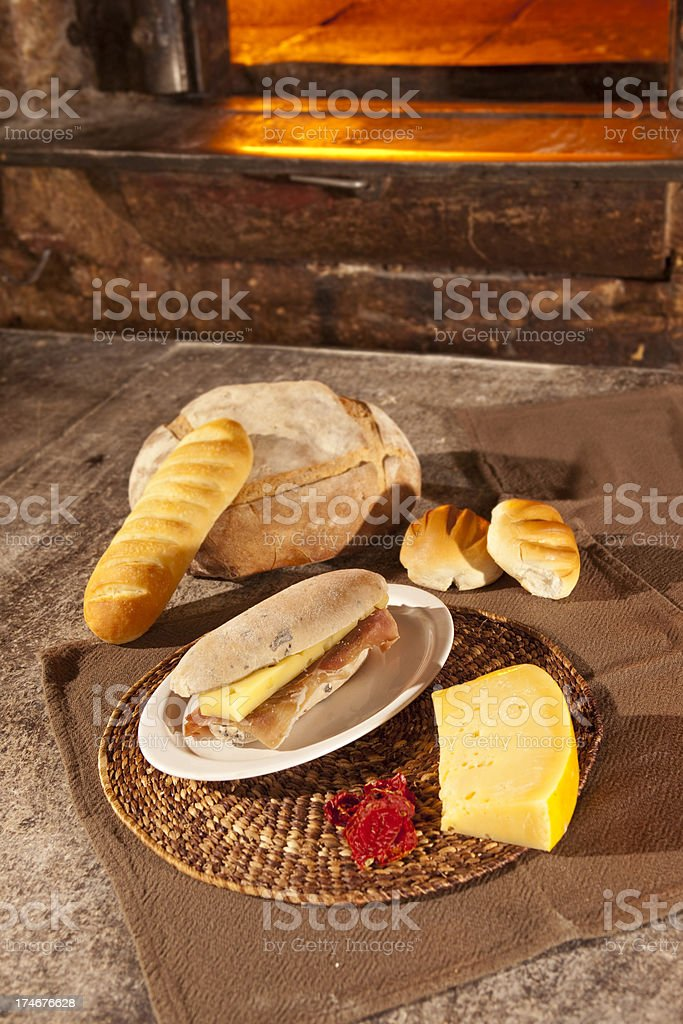 Fresh cheese and bacon sandwich near open fireplace stock photo
