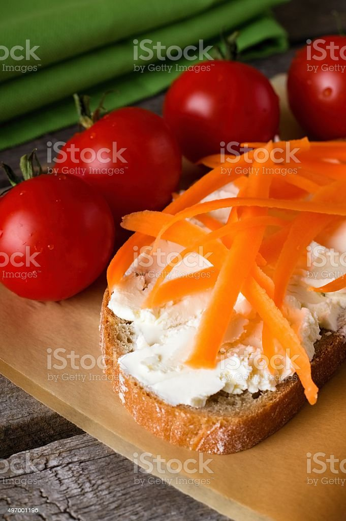Fresh cheese on slice of bread with carrot shaves stock photo