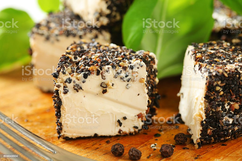 Fresh cheese rolled in pepper stock photo