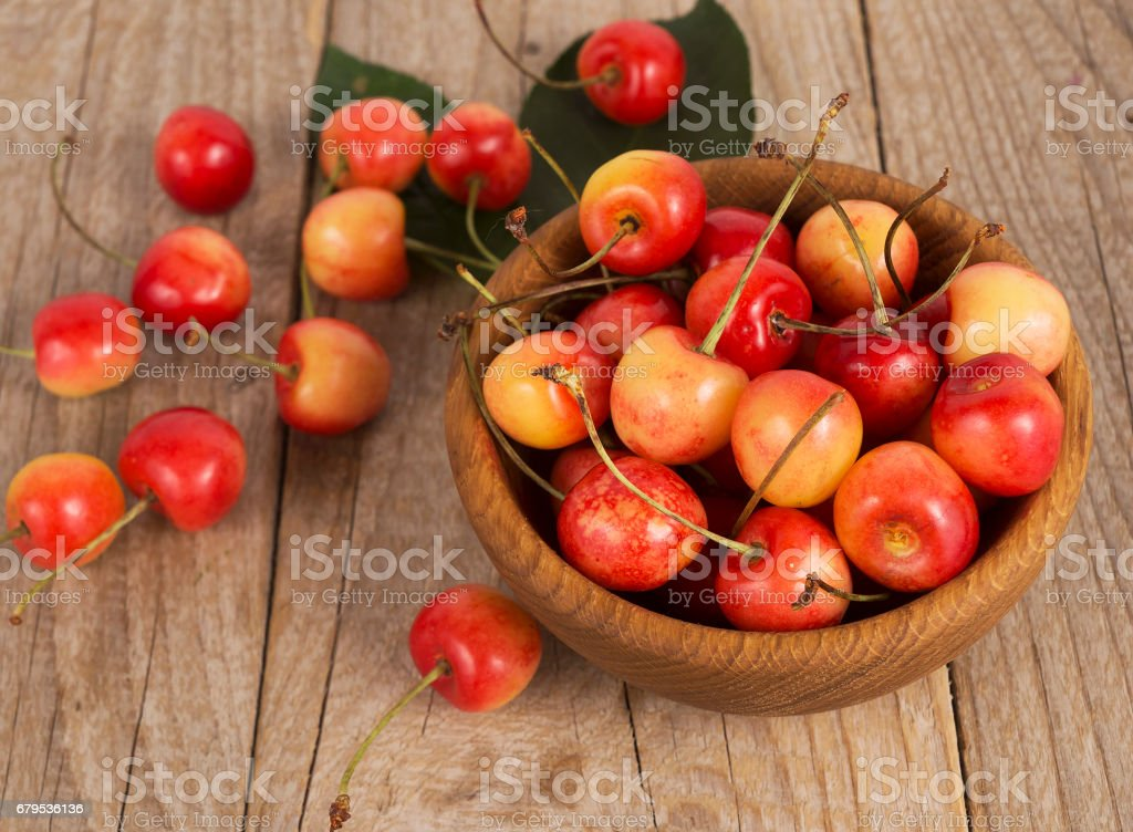 Fresh cherries scattered on a wooden table. Top view. stock photo